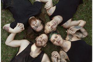 O grupo Francisco El Hombre deitados na grama