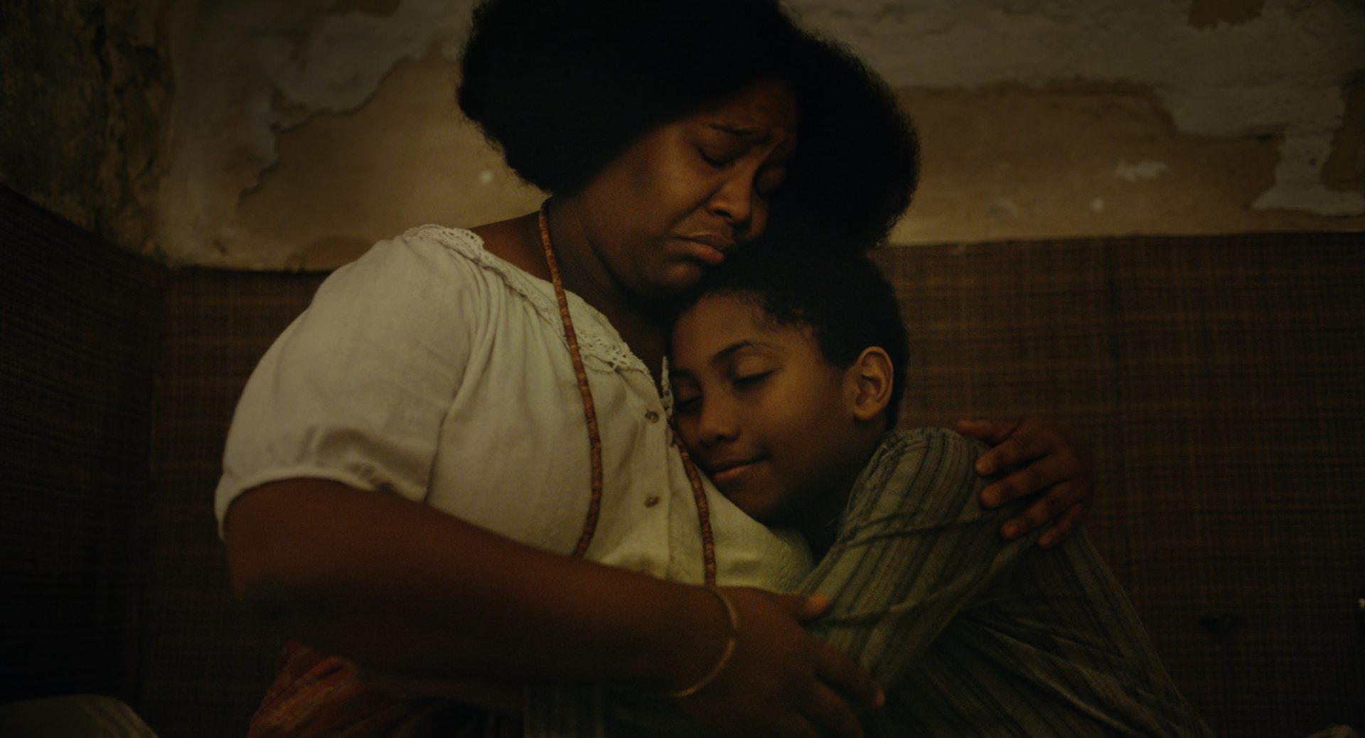 Mulher e menino se abraçam