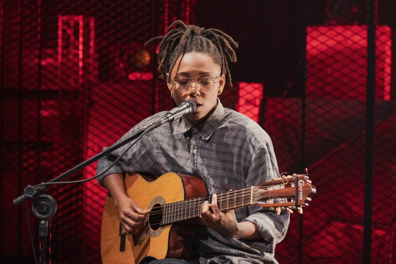 Bia Ferreira tocando violão e cantando